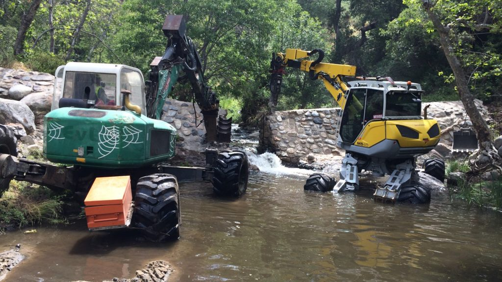 spider excavators removing dam