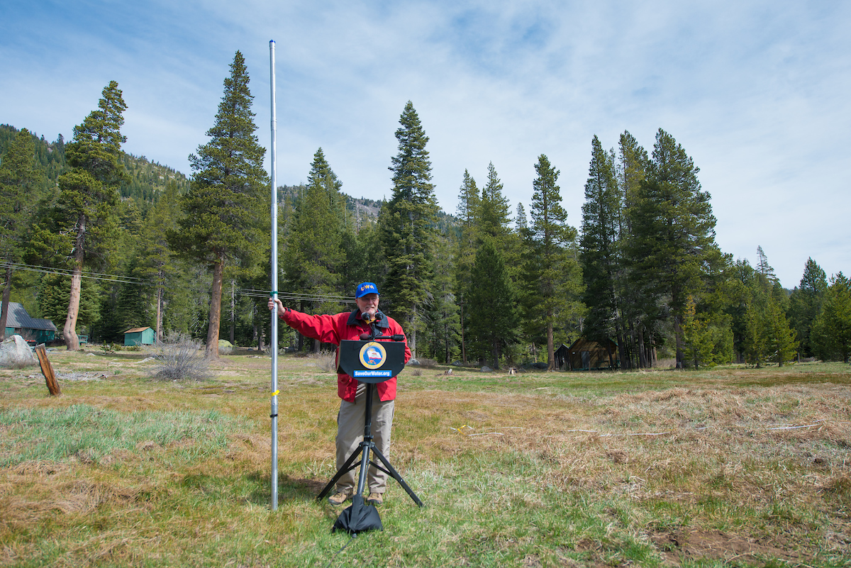 Frank Gehrke stands in a field with no snow holding the measuring pole.