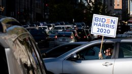 car driving with Biden-Harris sign.